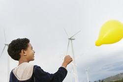 African American little boy playing with balloon at wind farm