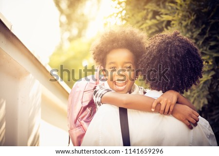 African American little girl in fathers hug. Looking at camera. Close up. - Shutterstock ID 1141659296