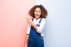 african american little girl looking excited and surprised pointing to the side and upwards to copy space against flat wall