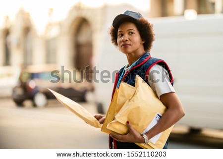 African American mailwoman delivering packages and looking away in the city.