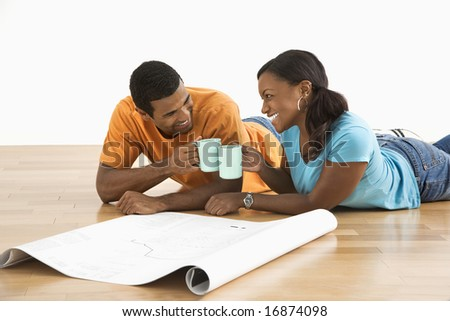African American male and female couple with architectural  blueprints toasting with their coffee cups.