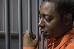 African American male behind bars in a jail cell