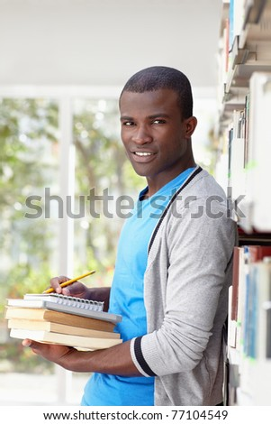 african american male college student leaning on shelf in library and looking at camera. Vertical shape, waist up, front view