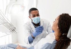 African american male dentist making treatment in modern clinic