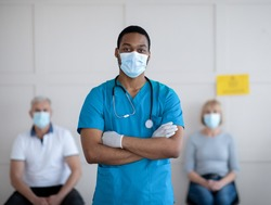 African American male doctor in face mask posing with crossed arms and looking at camera in clinic, mature patients waiting for covid-19 vaccination on background. Healthcare and medicine concept