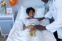 African american male doctor reassuring smiling sick mixed race girl in hospital bed holding teddy. medicine, health and healthcare services.