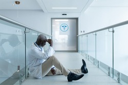 African american male doctor sitting in hospital corridor taking rest and ruminating. medicine, health and healthcare services.