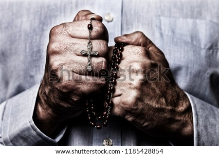 African American male hands praying holding a beads rosary with Jesus Christ in the cross or Crucifix on black background. Mature Afro American man with Christian Catholic religious faith Stock photo ©