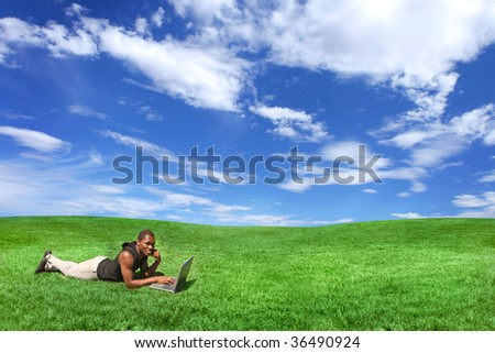 African American Male Outdoors on a Laptop on Grass