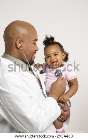 African-American male pediatrician holding and examinating baby girl with stethoscope. #2934463