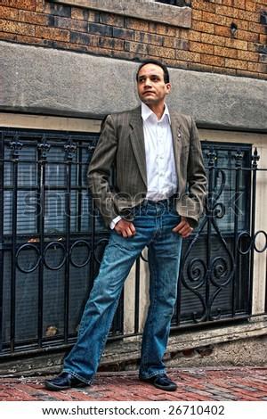 african american male posing on the sidewalk  wearing dress shirt , suit coat, blue jeans looking up street in beacon hill boston massachusetts