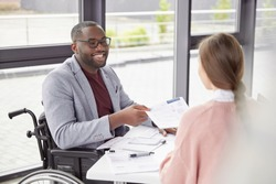 African American male sits at workplace in wheelchair, shares creative ideas and opinions with female worker, demonstrate new business project have informal meeting. Physically handicapped man