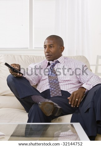 African American male watching TV while sitting on the coach in a shirt and tie. vertical.