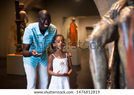 African American man and his daughter visiting exposition of museum with exhibits of medieval art