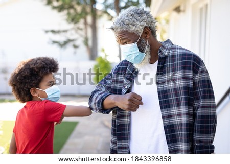 African American man and his grandson, wearing face masks, touching elbows, greeting. Social distancing and self isolating at home during Coronavirus Covid 19 quarantine lockdown. Foto stock ©