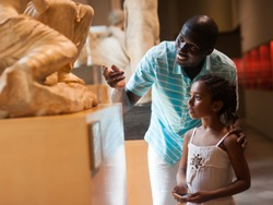 African American man and his little daughter looking at exhibits of antique sculpture at historical museum