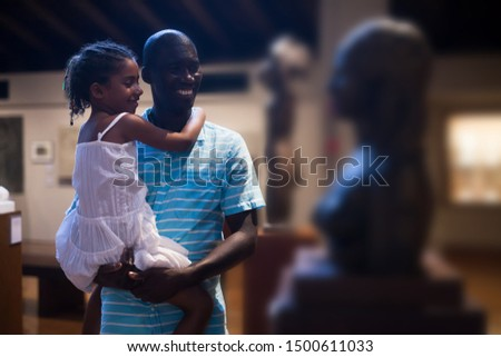 African American man and his little daughter visiting Art Museum with exhibits of modern sculpture