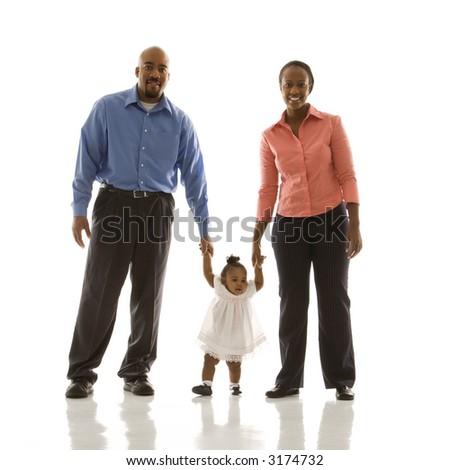 African American man and woman standing holding up infant girl by her hands against white background. - stock photo