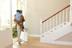 African American man arriving home carrying his young son through the open front door into the hallway. Social distancing and self isolation in quarantine lockdown for Coronavirus Covid19