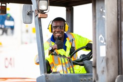 African American Man at work. Professional operation engineering. Young worker forklift driver wearing safety goggles and hard hat sitting in vehicle in warehouse