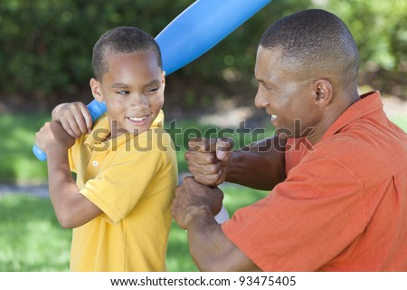 African American man & boy child, father and son playing baseball together outside. stock photo