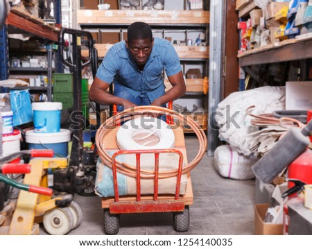 African-American man carrying handcart with purchases in building materials supermarket - Shutterstock ID 1254140035