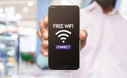 African american man demonstrating smartphone connected to free wifi hotspot in shopping center, selective focus on device