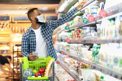 African American Man Doing Grocery Shopping In Supermarket, Wearing Protective Face Mask, Buying Food During Coronavirus Pandemic Outbreak Walking With Trolley In Store. Customer In Groceries Shop