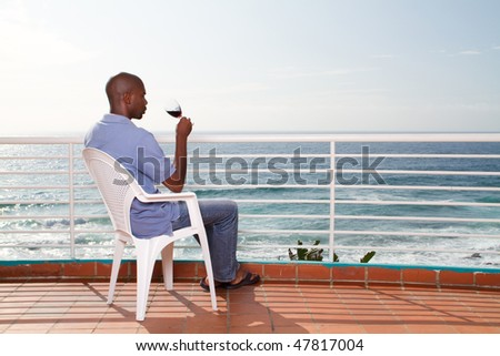 african american man drinking wine and viewing seascape