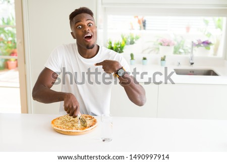 African american man eating cheese pizza at home with surprise face pointing finger to himself
