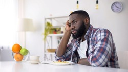 African-American man having no appetite, eating disorder, depression problem