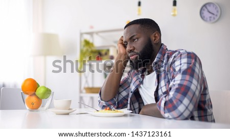 African-American man having no appetite, eating disorder, depression problem Stock photo ©