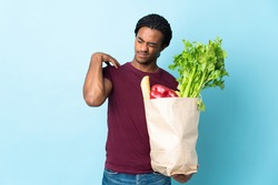 African American man holding a grocery shopping bag isolated on blue background suffering from pain in shoulder for having made an effort