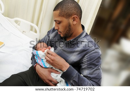 African American Man Holding Feeding Healthy Newborn Infant Baby Child in Hospital Room