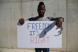 African-american man holds up a banner that reads freedom is a right. The man holds a shackle or handcuffs in his left hand. Human rights. Stop racism. Black lives matter.