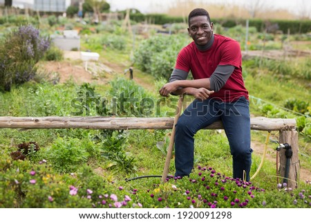 African american man horticulturist with mattock in garden outdoor Stock photo ©