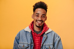 African American man in denim jacket smiling on orange background. Joyful guy in red hoodie posing hapily on isolate backdrop