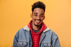 African American man in denim jacket smiling on orange background. Joyful guy in red hoodie posing hapily on isolate backdrop