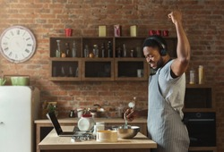 African-american man in earphones listening to music and dancing while baking in kitchen