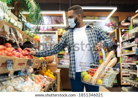 African American Man In Mask Doing Grocery Shopping Buying Vegetables And Fruits In Supermarket, Walking With Basket Full Of Food In Store. Male Customer In Groceries Shop Concept Photo stock ©