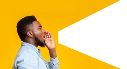 African american man making loud announcement at copy space, holding hand near his open mouth over yellow background, side view