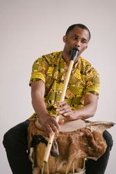 African american man musician playing the flute at white background copy space. Online musical class learning musical instruments. Rhythm and blues style. Ethnic culture and traditions.