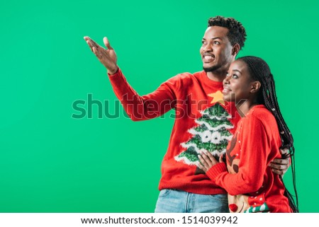 African American man pointing with hand near woman in Christmas sweater isolated on green #1514039942