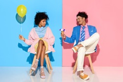 african american man presenting flowers in ice cream cone to girlfriend while sitting on chairs against pink and blue wall backdrop