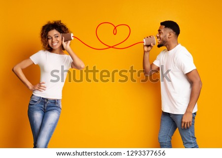 African-american man singing love song to his girlfriend via tin phone, orange studio background, copy space