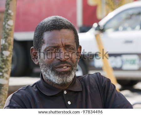 African American man sitting and relaxing outdoors during the daytime.