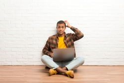 African american man sitting on the floor with his laptop with an expression of frustration and not understanding