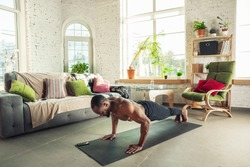 African-american man teaching at home online courses of fitness, aerobic, sporty lifestyle while being quarantine. Getting active while isolated, wellness, movement concept. Training, push-ups.