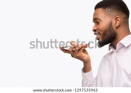 African-american man using voice assistant on mobile phone, talking to smartphone, isolated on white background, copy space #1297535962