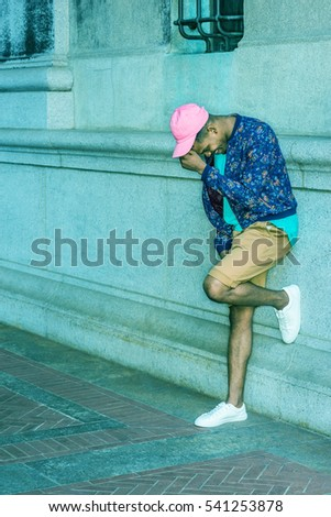 African American Man wearing blue patterned jacket, green shirt, yellow brown shorts, white sneakers, pink cap, standing by wall on street in New York, lowering head, smiling. Color filtered effect #541253878